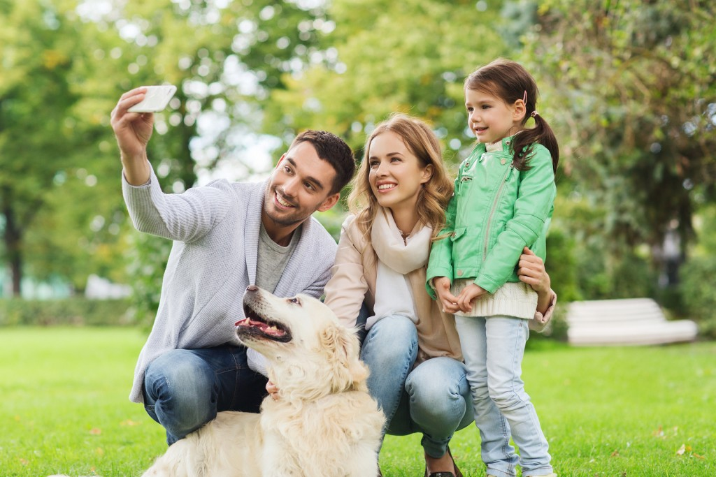 family, pet, animal, technology and people concept - happy famil