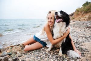Smiling charming young woman hugging her dog on the beach